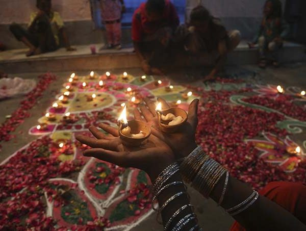 A Pakistani Hindu girl holds lamps as other decorate their house to celebrate Diwali, the Hindu festival of lights, in Karachi, Pakistan, Thursday, Oct. 19, 2017. (AP Photo/Shakil Adil)